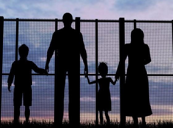 Porodica imigranata gleda kroz žicu